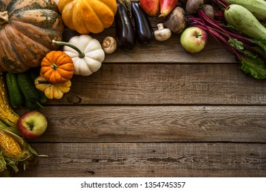 Frame of healthy organic vegetable. Farm fresh vegetables and fruits top view. Harvest vegetables with herb kitchen garden on wooden surface top view. Vegan food still life.