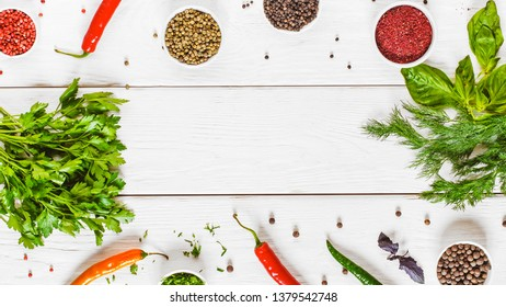 Frame of herbs and spices on white wooden background, flat lay. Top view on assortment of different colorful flavoring, free space. Mexican spicy food concept