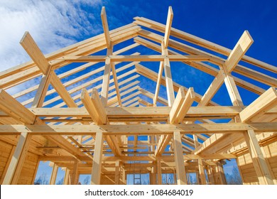 A frame of a house against a blue sky. The frame of the cottage. The beginning of the construction of the house. Construction site.