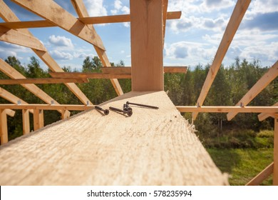 the frame of a house under construction close up and screws
