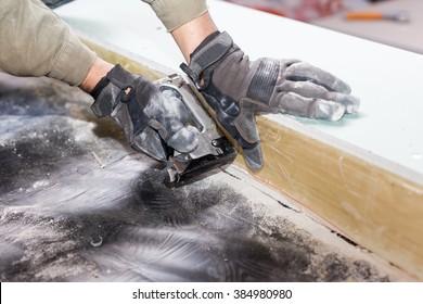Frame house wall construction. Worker attach a vapor barrier with staple gun