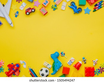 Frame of kids toys on yellow background with blank space for text. Top view, flat lay.
