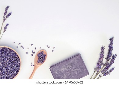 Frame from lavender flowers in wooden plate and spoon, soap, branches on white background, toned. Spa concept. Top view, close-up, flat lay, copy space, layout design