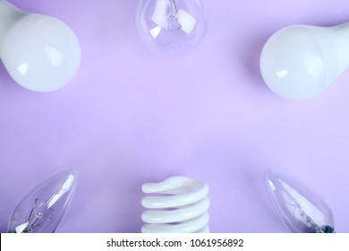 Frame of light bulbs on a pastel background of purple. Top view.