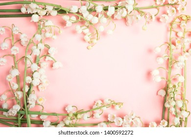 Frame of lily of the valley flowers on a pink background. Copy space, top view.