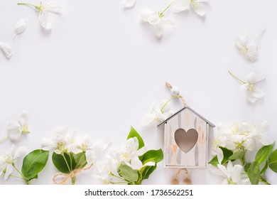 Frame made of apple blossom, birdhouse on white background. Flat lay, top view. Spring background