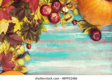 Frame made of autumn leaves, pumpkins, apples, chestnuts and wild grapes on old wooden background. Copy space. Toned image.