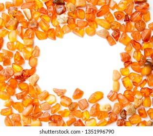 Frame made with chips of orange Baltic amber isolated on white. The Baltic region is home to the largest known deposit of amber, called Baltic amber or succinite. For making jewellery.