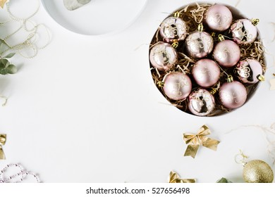 frame made of christmas decoration with christmas glass balls, tinsel, bow, eucalyptus. christmas wallpaper. flat lay, top view