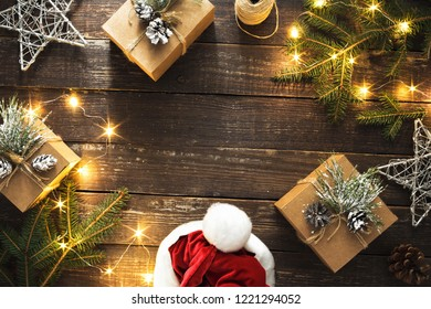 Frame made of Christmas decoration and christmas lights on dark wooden background top view. Flat lay Christmas background