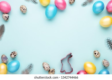 Frame made of colorful Easter eggs on turquoise background. Top view, copy spase, minimal styled.