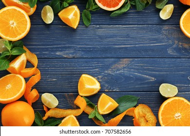 Frame made of delicious citrus fruits on wooden table