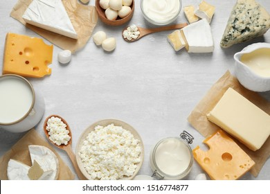 Frame made with different dairy products on white table, top view. Space for text