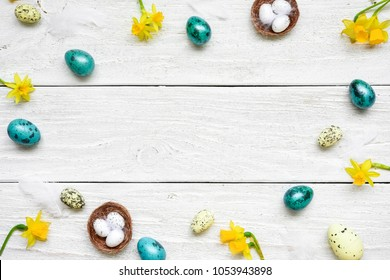 frame made of easter eggs and spring flowers on white wooden background. easter composition. top view with copy space