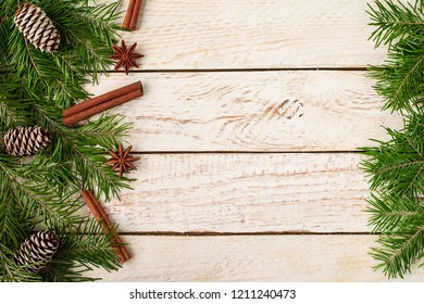 Frame made of festive Christmas decor and fir branches on wooden background. New Year and Christmas celebration. Winter holidays concept.  Top View. Space for text