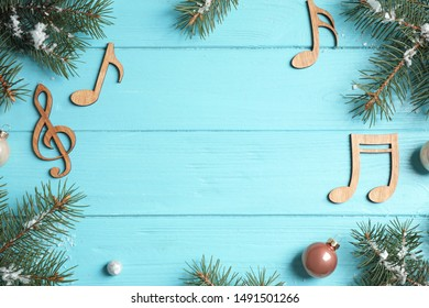 Frame made of fir branches and notes on blue wooden background, top view with space for text. Christmas music concept