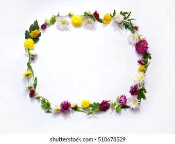 Frame made of flowers on white bright background, flat lay, top view. Spring concept. Pattern with space for text box