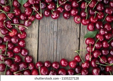 Frame, made of fresh picked cherries on rustic wooden background.