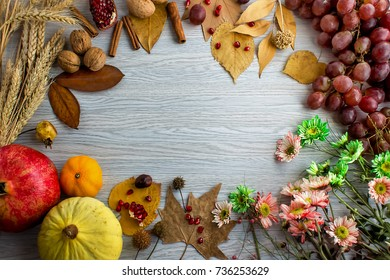 A frame made with grapes, melon, pomegranate, wheat, flowers, walnuts and autumn leaves. Harvest, autumn and Thanksgiving background with a space