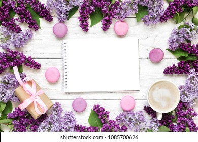 frame made of lilac flowers with blank greeting card or wedding invitation with coffee cup, gift box and macarons over white wooden table. mock up. flat lay. top view. mothers day background