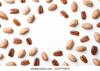 Frame made of pecan nuts on white background, top view with space for text