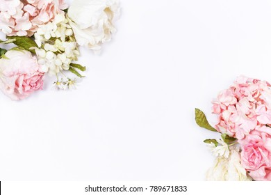 Frame made of pink and beige roses, hydrangea, green leaves, branches on white background. Flat lay, top view. Wedding's background. Valentine's background with copy space.