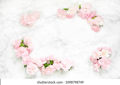 Frame made of pink carnations on marble background. Flat lay, top view
