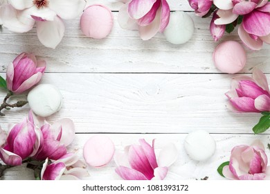 frame made of pink magnolia flowers with macarons over white wooden table. mock up. flat lay. top view. wedding or mothers day background