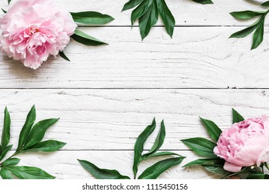 frame made of pink peony flowers over white wooden table with copy space. wedding invitation. top view. flat lay. nature concept