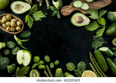Frame made of raw green vegetables, fruits and herbs.. Being fit and healthy concept. Place for text in the middle. Black board background