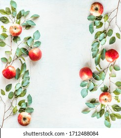 Frame made with red apples and green branches with leaves on white desk background. Top view. Flat lay. Border of apples. Food layout background