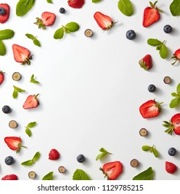 A frame made of ripe sweet halves of strawberries, blueberries and mint leaves on a gray background with copy space. Flat lay