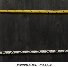 frame made of ropes for climbing. Mountaineering background. Two ropes on black wooden board