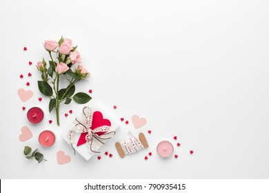 Frame made of rose flower, gift and candles on white background. Flat lay, top view, copy space.