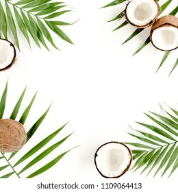 frame made of tropical green palm leaf and cracked coconut on white background. Nature concept. flat lay, top view