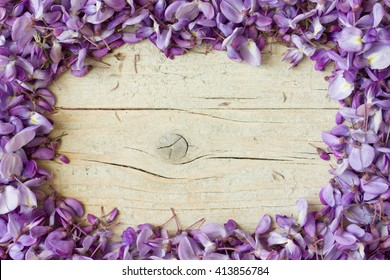 Frame made of violet wisteria flowers on white wooden background. Top view with copy space.