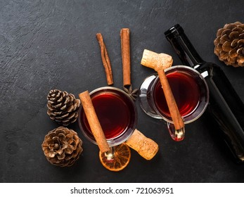 Frame of mandarines and twigs tree with two glasses of hot mulled wine with oranges and spices. Xmas handmade decoration on white table viewed from above. Flat lay, top view
