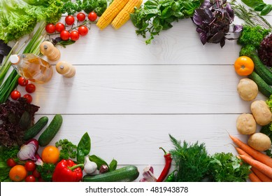 Frame for menu or recipe, fresh organic vegetables on white wood background. Healthy natural food on rustic wooden table with copy space. Bright vegetarian cooking ingredients top view