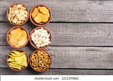 Frame . Mix of snacks : pretzels , crackers , chips nachos and pop corn