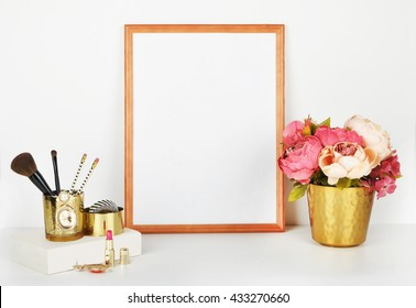 Frame Mock-up for your photo or text . Place your work. Wood frame with gold vase and gold items. Makeup items with gold vase and peonies. White book.