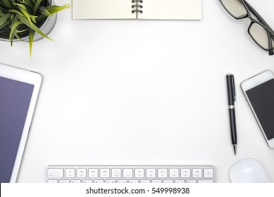 Frame with modern office supplies on white desk table with copy space view from above, flat lay style