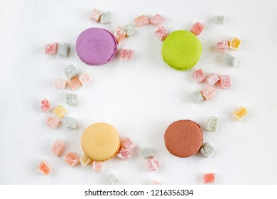 Frame from multicolored french macarons and lokum on white background. Confectionery, recipe, menu concept. Top view, flat lay, copy space, layout design.