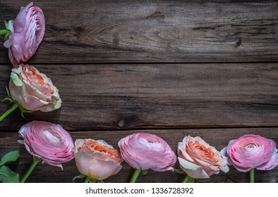 Frame of multicolored roses on an old wooden surface. Top view.Copy space.