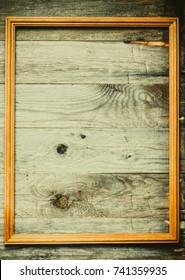 Frame on a wooden rustic texture for background. Rough weathered wooden board. Toned.