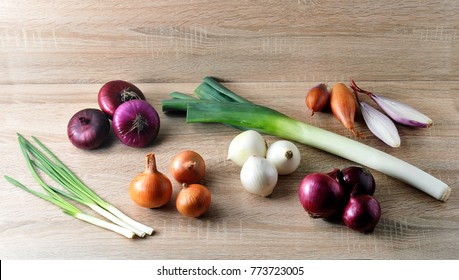 In the frame, onions, leeks, shallots, white, sweet red, yellow onions, green onions. Light wooden background. Close-up.