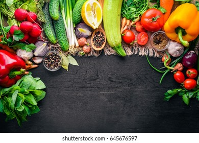 Frame of organic food. Fresh raw vegetables and spices. On a wooden chalkboard.