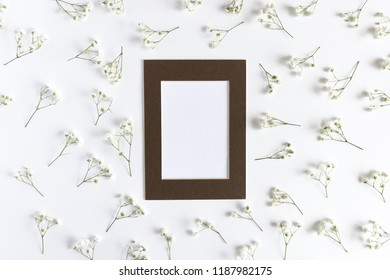 Frame with paper card mockup. Floral pattern made of white gypsophila on a white background