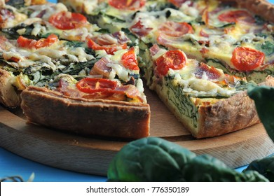 In the frame, part of the French classic pie quiche with spinach, bacon, cherry tomatoes and cheese. The pie on the wooden board is cut into portions. Blue background. Close-up. Macro photography.