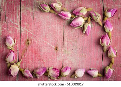 Frame of pink dried roses on wooden background. Top view with copy space. Sweet rustic card.