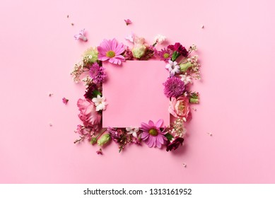 Frame of pink flowers over punchy pastel background. Valentines day, Woman day concept. Spring or summer banner with copy space.